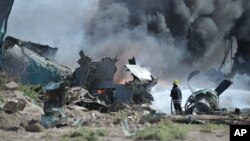 Nhân viên cứu hỏa cố gắng dập tắt ngọn lửa chiếc máy bay của Ethiopia rơi và bốc cháy tại phi trường ở Mogadishu, Somalia, 9/8/13