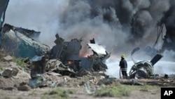 Bombeiros da missão de manutenção das paz da União Africana tentam combater o incêndio provocado pela queda do avião
