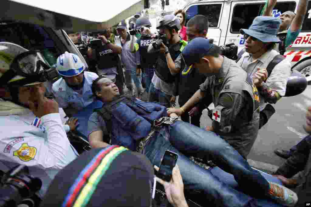 A local journalist is carried away by medics after being wounded from an explosive thrown towards riot police trying to retake a protest site in Bangkok, Feb. 14, 2014.
