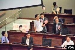 香港民主派立法會議員張超雄(右)及朱凱迪在財委會會議站立抗議
