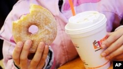 "FILE - A girl has a doughnut and a beverage in New York, Feb. 14, 2013. A new study finds more than half the calories consumed in the average American diet comes from ""ultra-processed"" foods, including sugary drinks."