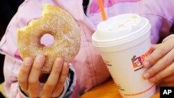 Ảnh tư liệu - Một bé gái cầm bánh và thức uống ở New York, ngày 14 tháng 2 năm 2013. Một nghiên cứu mới cho thấy hơn một nửa lượng calories tiêu thụ trong chế độ ăn uống trung bình của người Mỹ là từ thực phẩm chế biến sẵn, bao gồm thức uống có đường.