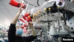 中国浙江湖州一名戴着口罩的工人在生产线上生产出口的袜子。(2020年2月19日)