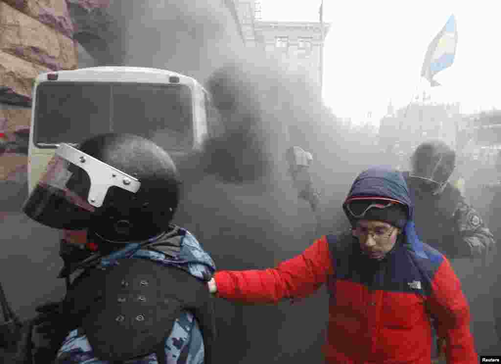 Riot police leave a bus after protesters threw a smoke bomb, outside City Hall in Kyiv, Dec. 11, 2013.