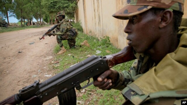 Somali National Army soldiers serving with the AU Mission in Somalia hold defensive positions in the town of Afgoye