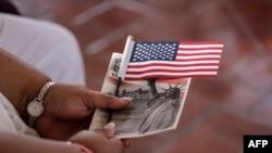 Seorang perempuan memegang bendera AS dalam upacara naturalisasi khusus sebelum menjadi warga negara AS di New York, 16 September 2016. (FOto: dok).