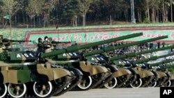 Tentara militer Myanmar memberikan hormat dari tank ketika melewati tempat perayaan kemerdekaan ke-67 di Naypyitaw, Myanmar, Minggu, 4 Januari 2015. (AP Photo/Khin Maung Win)