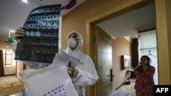 中國湖北省武漢市一家醫院身著防護服的醫生正在檢查一名病人的肺部CT片子。(法新社2020年2月3日資料照)