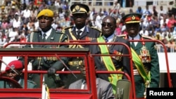Zimbabwe's President Robert Mugabe (2nd R) arrives at the 32nd anniversary celebrations of the Zimbabwe Defense Forces Day at the National Sports stadium, in Harare, August 14, 2012.