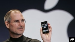 In this Jan. 9, 2007 file phtoo, Apple CEO Steve Jobs holds up an Apple iPhone at the MacWorld Conference in San Francisco. Apple Inc. on