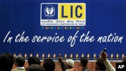 Indian bystanders watch an art performance in front of a billboard for the Life Insurance Corporation of India (LIC) outside the company's offices in New Delhi, India, Nov. 25, 2010. Eight senior officials from some of India's top financial services comp
