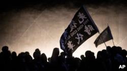 """Người biểu tình phất cờ ghi hàng chữ """"Tự do cho Hong Kong, Cách mạng Bây giờ"""" trong cuộc tuần hành gần Bảo tàng Nghệ thuật Hong Kong, ngày 13/12/2019."""