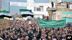 시리아 홈스에서 바샤르 알 아사드 대통령 퇴진을 요구하며 시리아 혁명기를 들고 시위를 벌이는 반정부 시위대