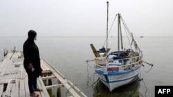 Aminata Traoure, 28-godišnja izbjeglica iz Obale Bjelokosti koja je početkom marta preživjela brodolom dok je pokušavala doći do Evrope, 22. aprila 2021. gleda čamac u obalnom gradu Tunisa, Sfaxu, oko 270 km jugoistočno od glavnog grada. .