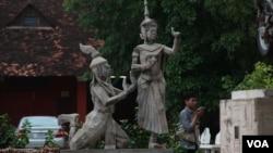 A man walks pass by a statue of Moni Mekhala, goddess of the seas, and Ream Eyso, storm demon, inside Royal University of Fine Art on May 28, 2015. (Nov Povleakhena/VOA Khmer)