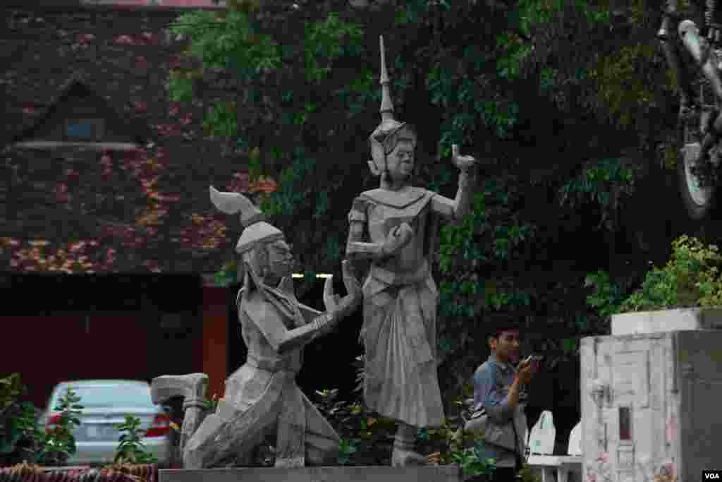 A man walks pass by a statue of Moni Mekhala, goddess of the seas, and Ream Eyso, storm demon, inside Royal University of Fine Arts on May 28, 2015. (Nov Povleakhena/VOA Khmer)