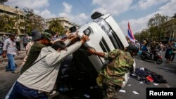 태국 방콩 정부청사 인근에서 18일 반정부 시위대가 경찰차를 뒤집고 있다. 이 날 시위대와 경찰의 충돌로 4명이 숨지고 60여명이 다쳤다.