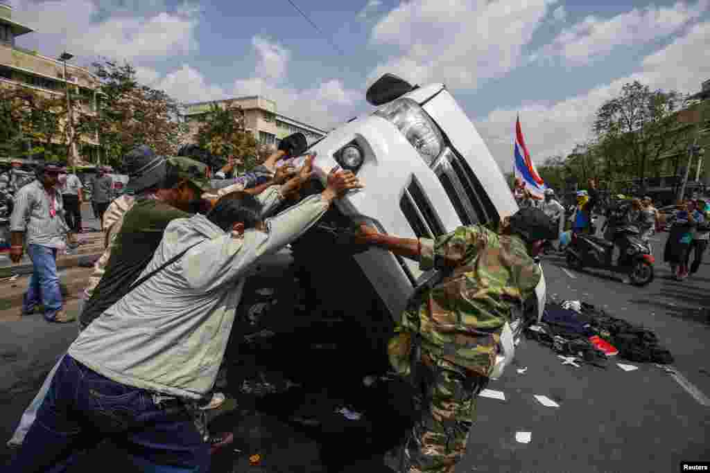 Anti-government protesters lift a police car after clashes with Thai riot police officers, near Government House, Bangkok Feb. 18, 2014.
