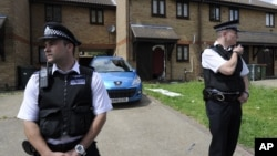 Police officers outside home raided in Stratford, east London, July 5, 2012.