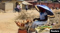 A woman roasts maize by the road side along Manchock road, in Kaura Local Government Kaduna State, Nigeria, March 21, 2014.