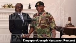 In this handout photos, President Robert Mugabe poses with General Constantino Chiwenga at State House in Harare, Zimbabwe, Nov. 16, 2017.