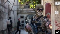 İraq təhlükəsizlik qüvvələrinin maskalı əsgəri Mosulda İŞİD militantlarına qarşı reyd zamanı