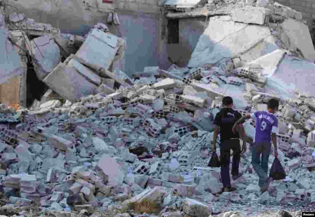 Boys walk on the rubble of damaged buildings in Duma neighborhood of Damascus, Sept. 23, 2013.