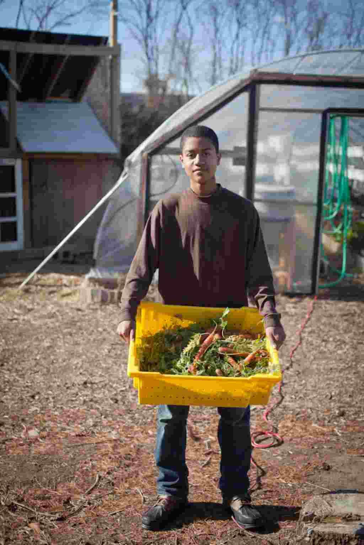 El voluntario John Clark muestra la cosecha de zanahorias de la granja.