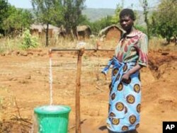 A woman in Mwanza, Malawi, collects tap water. Ecological economist Keven Urama calls for better water management to save rainwater for dry periods.