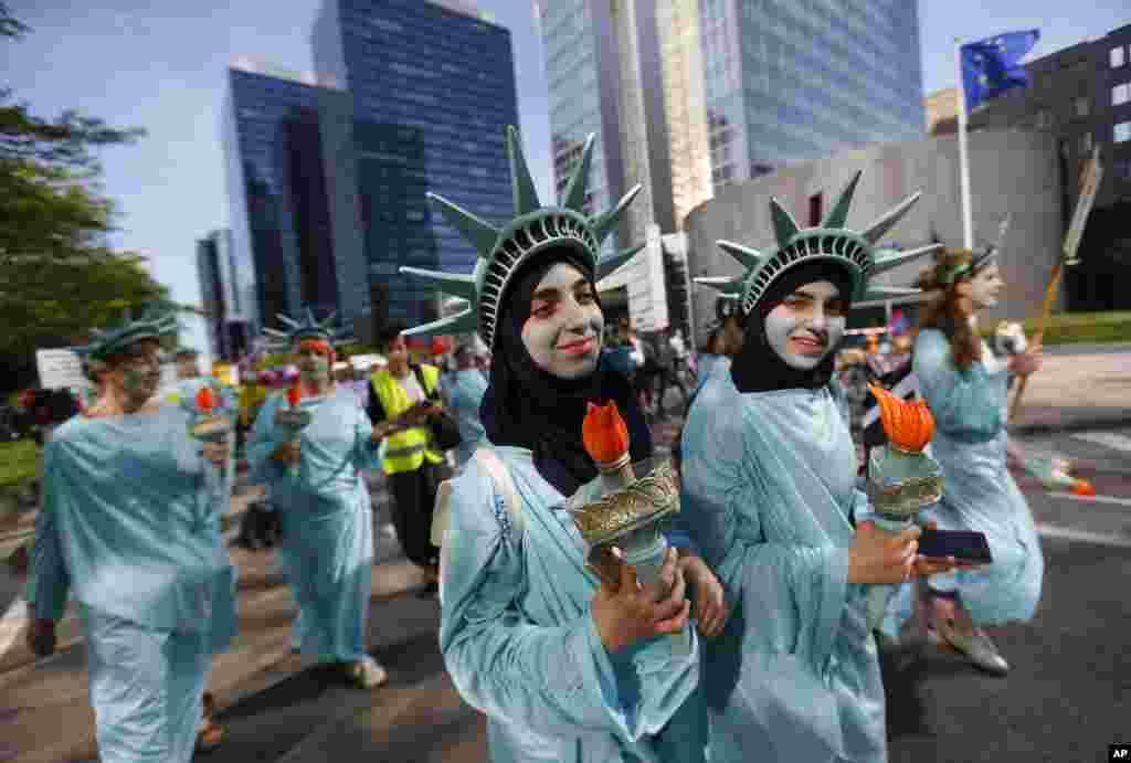 Para demonstran, termasuk dua perempuan berjilbab, mengenakan pakaian seperti Patung Liberty dalam demonstrasi di Brussels, Belgia menjelang kedatangan Presiden AS Donald Trump dan KTT NATO.