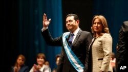 Guatemala's new President Jimmy Morales greets the public as he holds hands with his wife, first lady Hilda Marroquin, after he was sworn-in at the National Theater in Guatemala City, Thursday, Jan. 14, 2016.