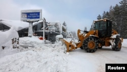 A plow clears snow after a heavy winter storm in Tahoe City, California, Jan. 11, 2017. The storm that struck California has moved to the Midwest, where it is leaving freezing rain and ice.
