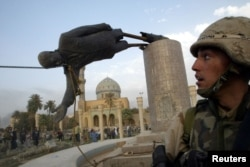 FILE - U.S. Marine Corp Assaultman Kirk Dalrymple watches as a statue of Iraq's President Saddam Hussein falls in central Baghdad, April 9, 2003.