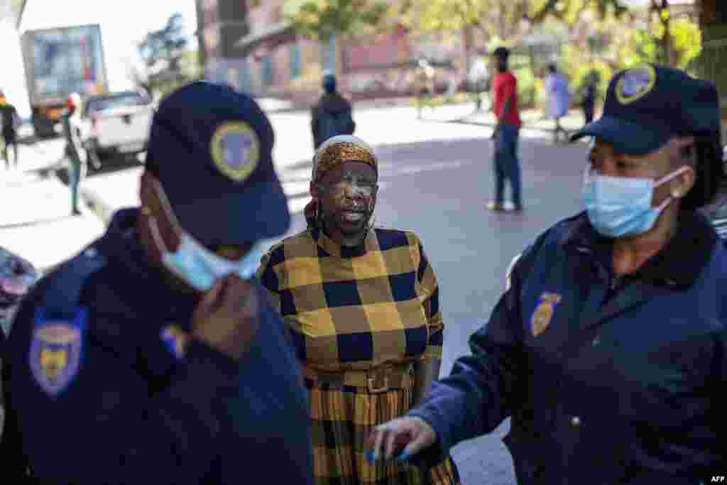 A woman reacts in pain after being pepper sprayed by a member of the South African Police Service, not visible, for not wearing a face mask, as members of the Johannesburg Metro Police Department walk away, in Hillbrow, Johannesburg.