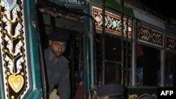 Полицейские выносят из автобуса жертву очередного теракта в Карачи. Пакистан. 2 августа 2010 года