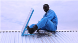 A worker installs a BBOXX solar panel on a rooftop in Kakuma, a refugee camp in northwest Kenya. (M. Yusuf/VOA)