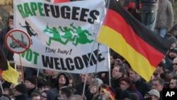 """La Droite manifeste avec une banderolle """"des réfugiés violeurs"""" ne sont pas les bienvenus - !Restez chez vous!"""" et un signe d'une mosquée barrée pendant leur marche a Cologne, Allemagne, samedi le 9 Janvier, 2016. Les femmes activistes de droite , des manifestants d'extrême-droite et de gauche, les contre- manifestants, sont tous descendus dans les rues de Cologne le samedi à la suite d'une vague de vols et d'agressions sexuelles du Nouvel An à Cologne blâmé en grande partie sur les étrangers . ( AP Photo / Juergen Schwarz )"""