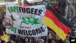 """Right-wing demonstrators hold a sign """"Rapefugees not welcome - !Stay away!"""" and a sign with a crossed out mosque as they march in Cologne, Germany, Jan. 9, 2016. Women's rights activists, far-right demonstrators and left-wing counter-protesters all took to the streets of Cologne on Saturday in the aftermath of a string of New Year's Eve sexual assaults and robberies in Cologne blamed largely on foreigners."""