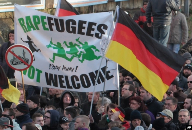 "Right-wing demonstrators hold a sign ""Rapefugees not welcome - !Stay away!"" and a sign with a crossed out mosque as they march in Cologne, Germany Saturday Jan. 9, 2016. Women's rights activists, far-right demonstrators and left-wing counter-protesters al"