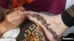 Chuyên viên thẩm mỹ trang điểm tay một khách hàng để chuẩn bị cho lễ hội Hồi giáo Eid al-Fitr ở thành phố Karachi, Pakistan.