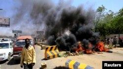 Les manifestants soudanais brûlent des pneus et bloquent la route menant au pont al-Mek Nimir qui passe sur le Nil Bleu. qui relie Khartoum Nord et Khartoum, au Soudan, le 13 mai 2019.