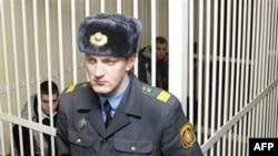 На заднем плане: Артем Бреус (справа) и Иван Гапонов (слева) в зале суда. Минск. Беларусь. 22 февраля 2011 года