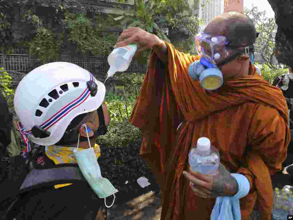 A Buddhist monk helps an anti-government protester clean his eyes with salt water solution after riot police fired tear gas in Bangkok, Dec. 2, 2013.