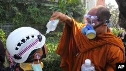 Một nhà sư giúp người biểu tình bị trúng hơi cay tại Bangkok, ngày 2/12/2013.