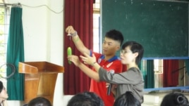 Phan Thi Hoai Yen guides students at a Vietnamese high school on how to use a condom. (Courtesy: AIESEC)