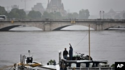 A man waves standing on a barge on the Seine river during floods, in Paris, June 5, 2016. Flooding in French capital is part of a weeklong deluge that has swamped large parts of Europe, killing at least 18 people in Germany, France, Romania and Belgium.