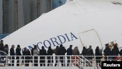 Familiares de los desaparecidos aprecian desde un ferry el crucero Concordia después de un año de la tragedia.