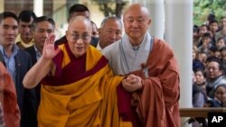 The Dalai Lama gestures as he arrives to give a religious talk at the Tsuglakhang temple in Dharamsala, India, Oct. 23, 2011.