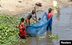 FILE - Children use a mosquito net to fish along the Nile river in South Sudan's capital of Juba, Jan. 8, 2011.