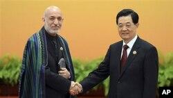 ປະທານປະເທດຈີນ ທ່ານ Hu Jintao (ຂວາ) ແລະ ປະທານາທິບໍດີອັຟການິສຖານ ທ່ານ Hamid Karzai ຖ່າຍພາບຮ່ວມກັນ ກ່ອນການປະຊຸມທີ່ສາລາປະຊາຊົນ ໃນກຸງປັກກິ່ງ ວັນພະຫັດ ທີ 7 ພຶດສະພາ 2012.